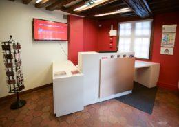 Roselier Agencement - Banque d'accueil - Pôle Muséal de la ville de Lisieux - Stratifié ton crème et cuivre brossé avec PMR rétractable sous le plateau du bureau